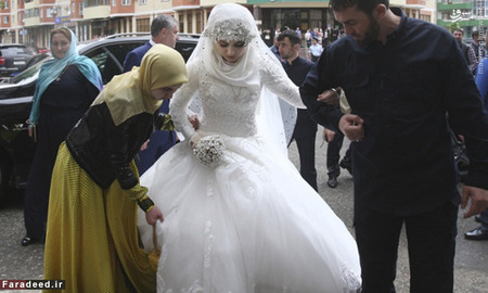 A bride, Chechen Kheda Goilabiyeva, is taken by head of the Chechen leader's administration Magomed Daudov to a wedding registry office for her wedding with Chechen police officer Nazhud Guchigov, in Chechnya's provincial capital Grozny, Russia, Saturday, May 16, 2015. A 46-year-old Chechen police officer taking a 17-year-old as his second wife in flagrant violation of Russian laws has caused a storm in the Russian media and put the region's ruler on the defensive. (AP Photo)